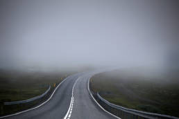 A winding road that leads into a patch of fog