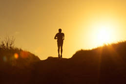 Sihouette of a person running with the sun setting